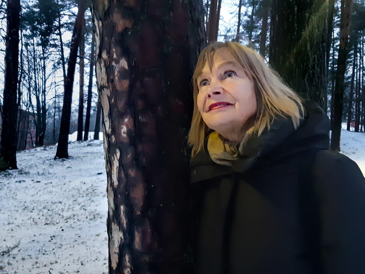 Nainen nojaa puuhun ja hymyilee.