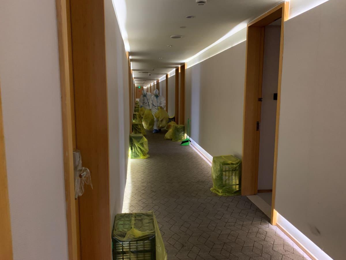kaksi siivoojaa valkoisessa suojapuvussa kerää keltaisia jätesäkkejä kapealta hotellikäytävältä ovien edestä Shanghain koronaviruskaranteenissa