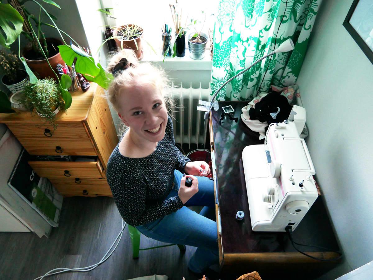 Hannele Kemppainen istuu ompelukoneen ääressä lankarulla kädessään.