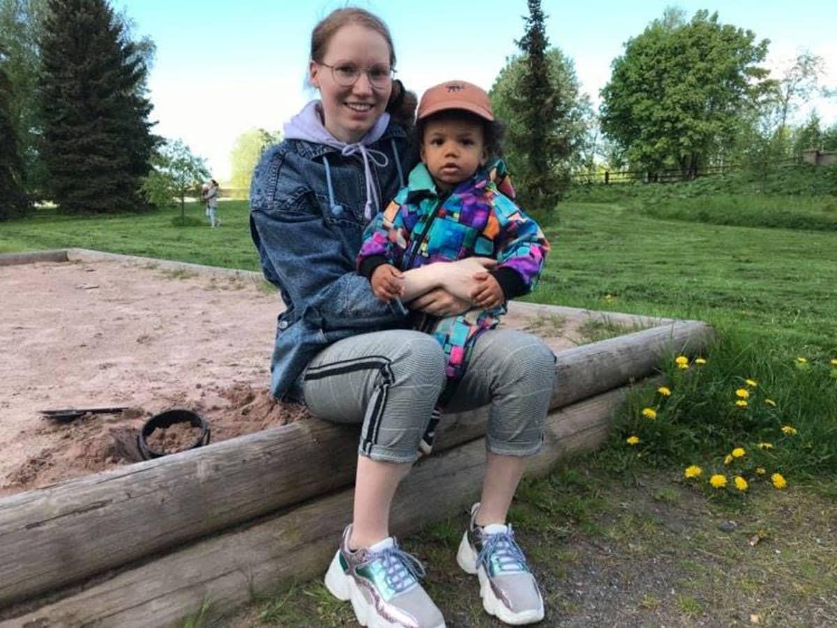 Äiti puistossa lapsensa kanssa.