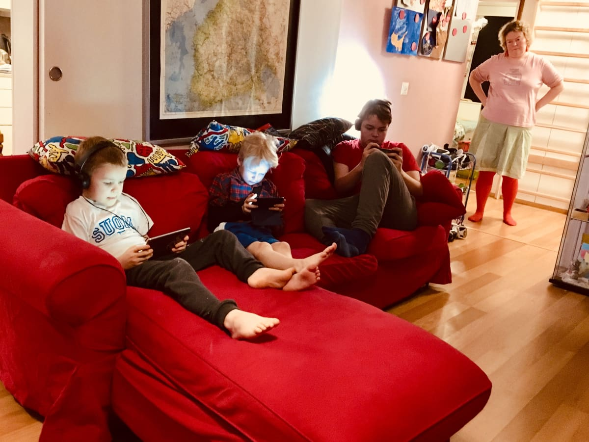 Kuvassa perheen pojat Olavi, Ilmari ja Emil pelaamassa, äiti Ilona vahtimassa ja avomies Kalle treeneissä.