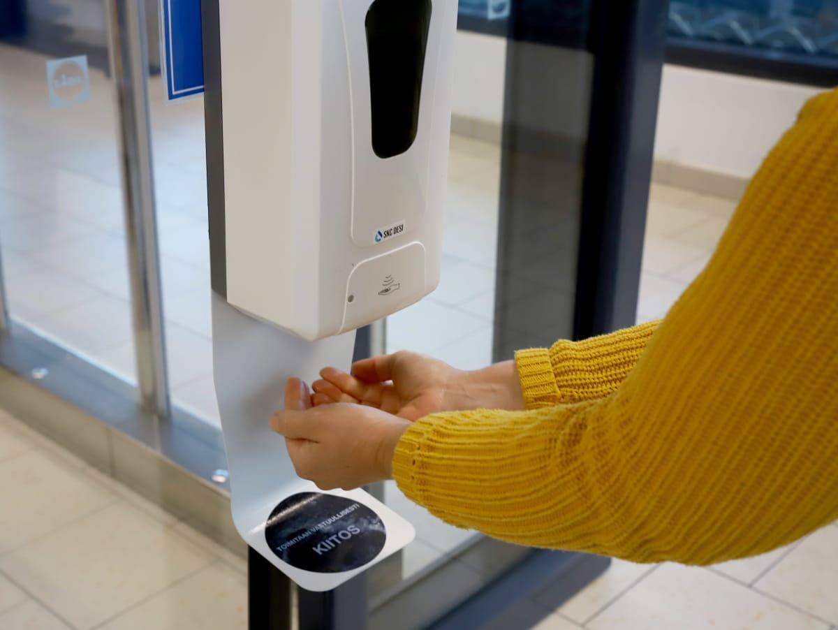 Asiakas ottaa käsihuuhdetta kaupan sisäänkäynnin automaatista
