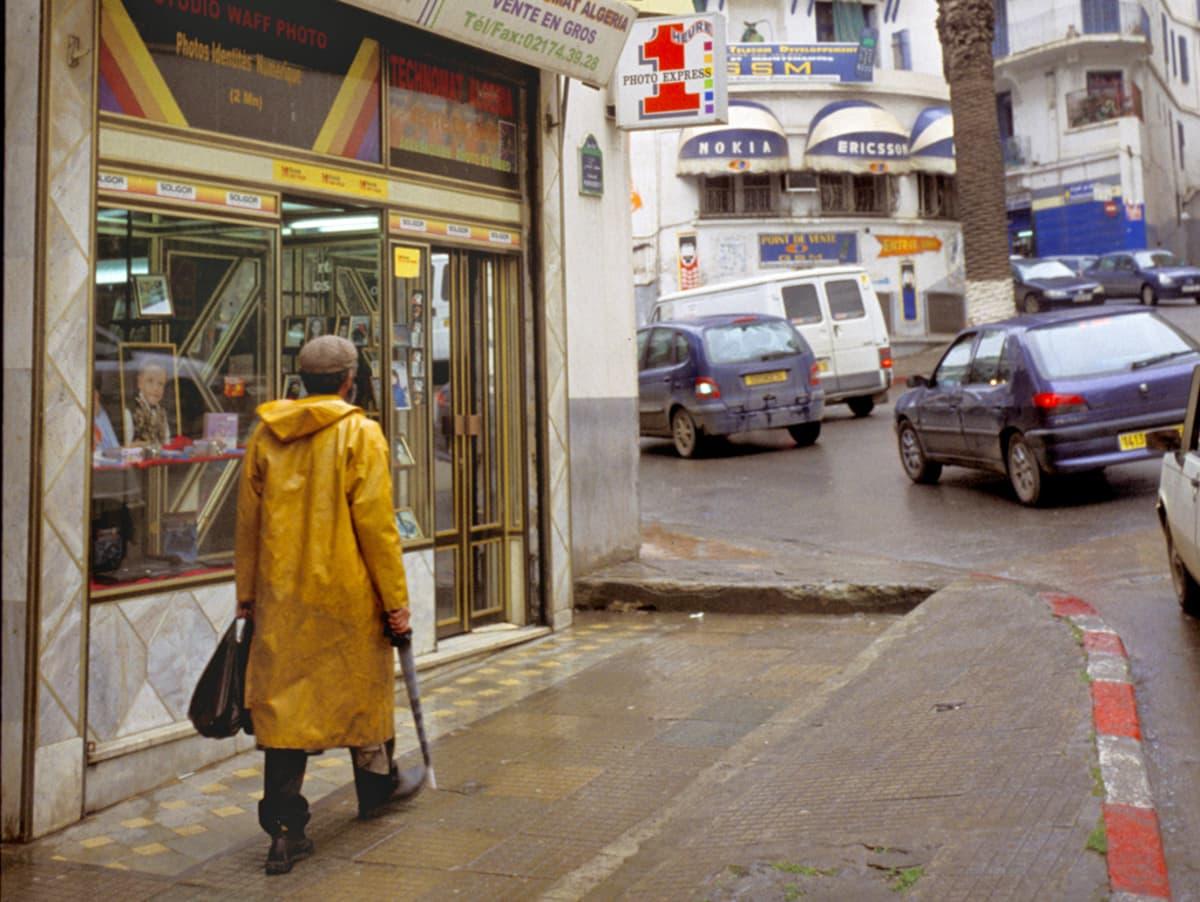 Sadetakkiin puketunt mies kävelee näyteikkunan ohi, kadulla autoja.