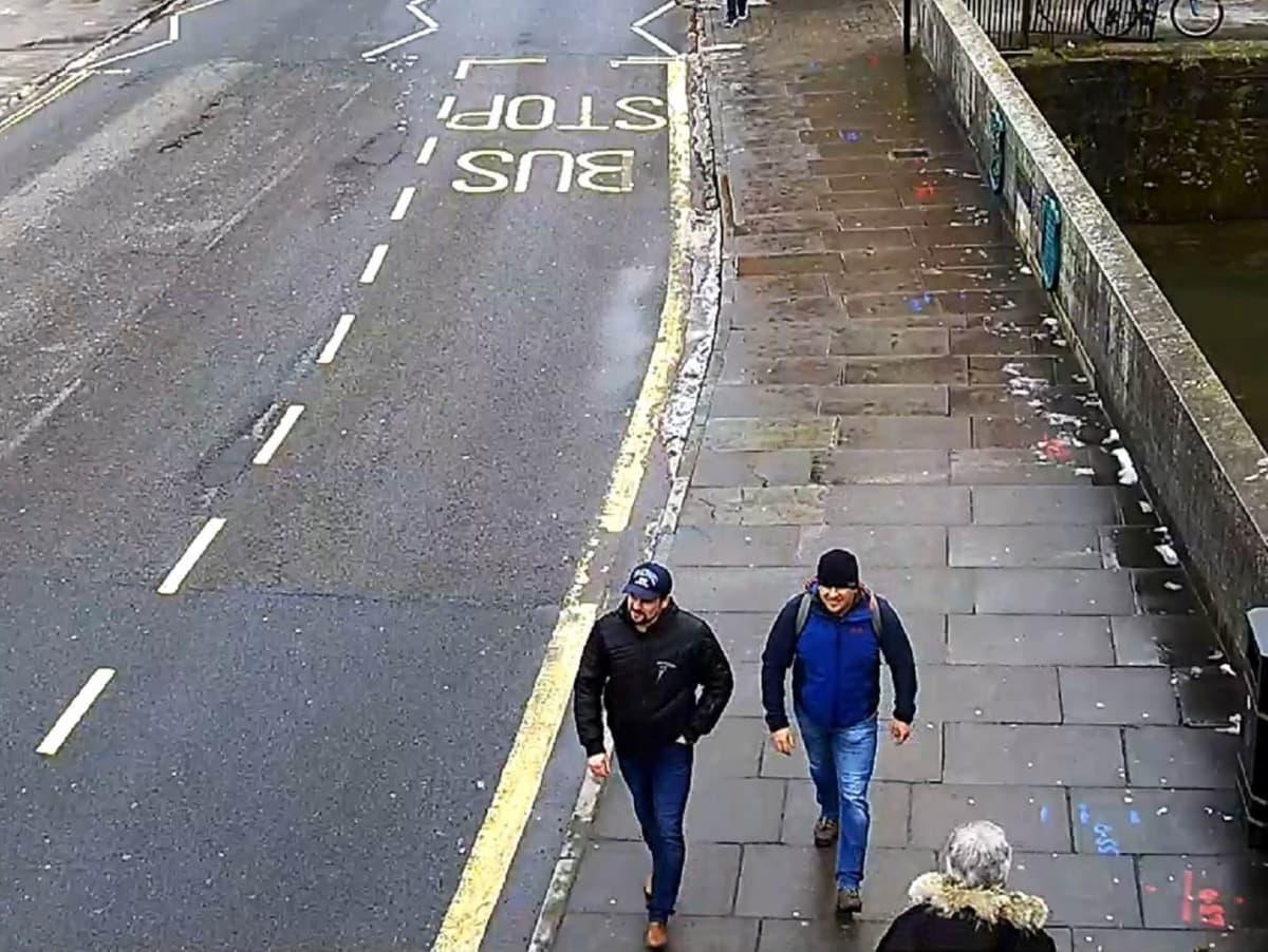Kaksi miestä kävelee kadulla. Toisella on sininen lippalakki, musta takki ja parta, toisella pipo, reppu selässään ja sininen takki. Molemmilla on siniset farkut.