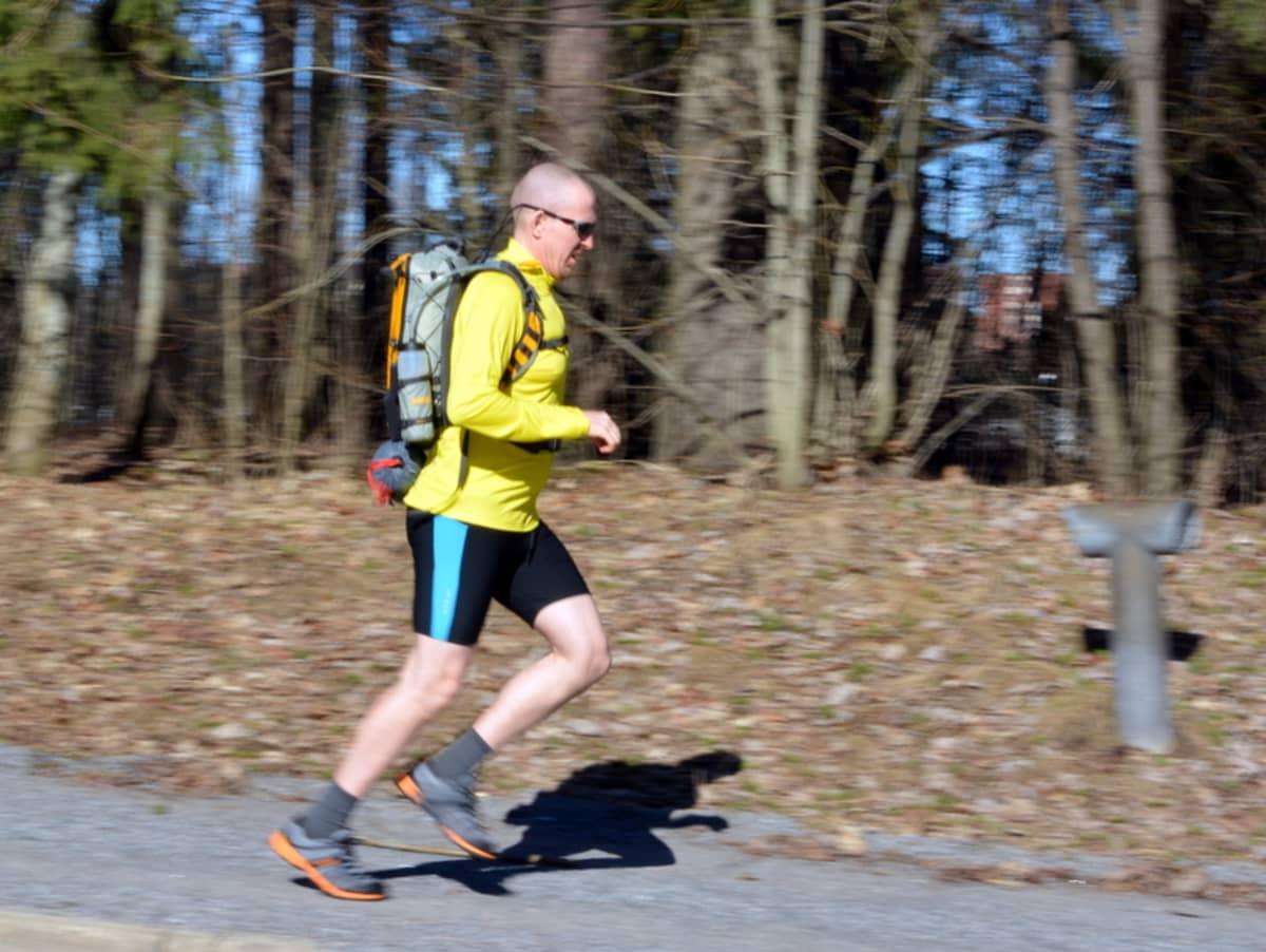 Mies juoksee keväisellä kadulla.