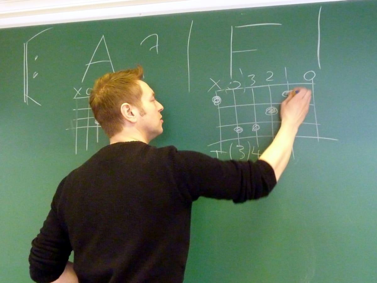 Opettaja kirjoittaa taululle musiikintunnilla.