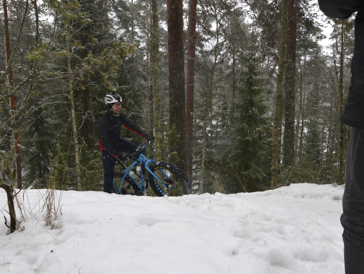 Maastopyöräilijä nousee lumista mäkeä