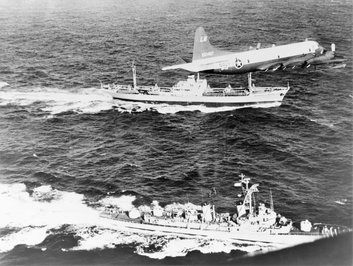 Ilmakuva merellä. Yhdysvaltain sota-alus seilaa neuvostoliittolaisen rahtialuksen vierellä. Ilmassa lentää yhdysvaltalainen lentokone.