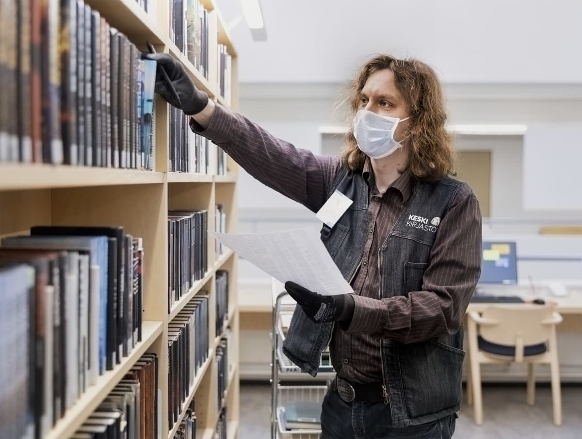 Viljami Marjomäki etsii kirjastokirjaa.