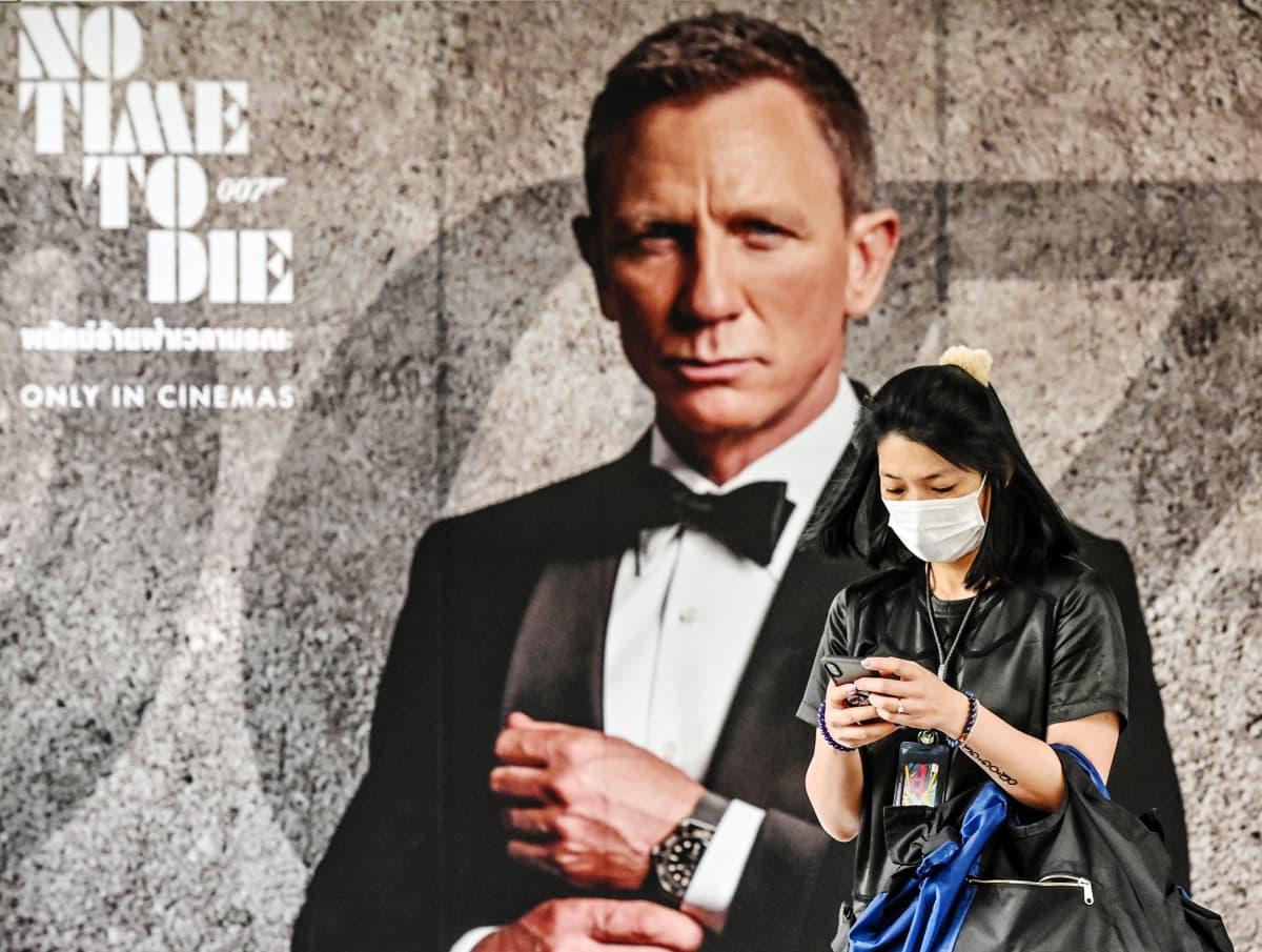 Kuvassa on No time to die -elokuvan juliste ja suojamaskia käyttävä nainen.