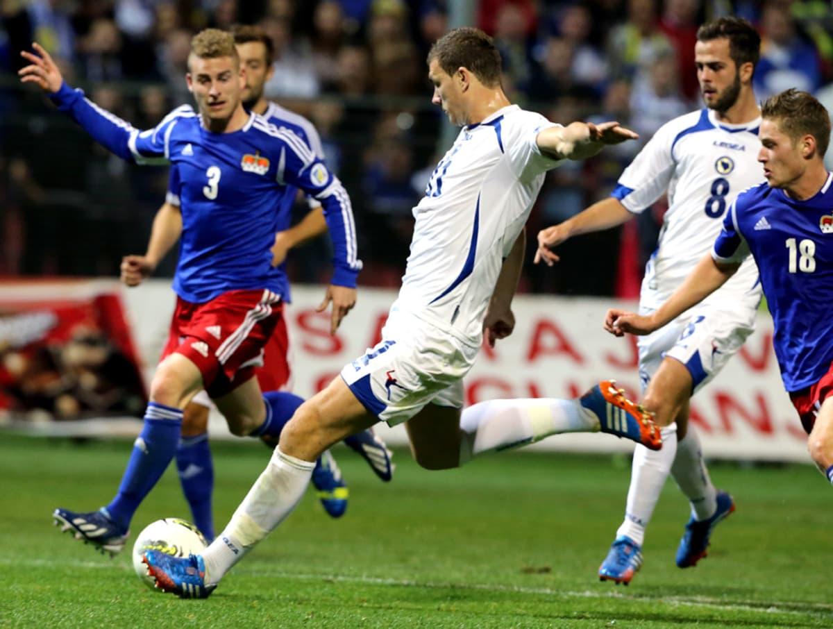 Bosnian Edin Dzeko (kesk.) laukoo Liechtensteinin puolustajien keskeltä.