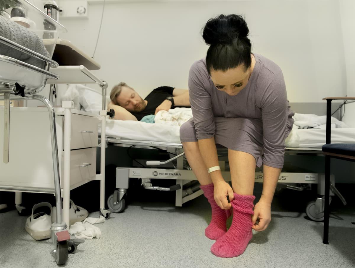 Sinikka Ijäs laittaa jalkaan valitsemaansa Marttojen ensisynnyttäjille neulomaa sukkaparia.