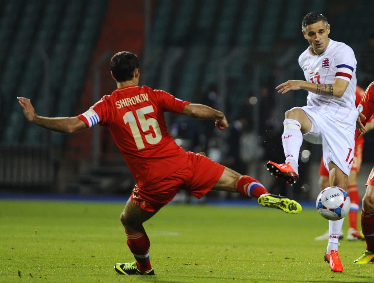 Venäjän Roman Shirokov ja Luxemburgin Mario Mutsh kamppailevat pallosta.