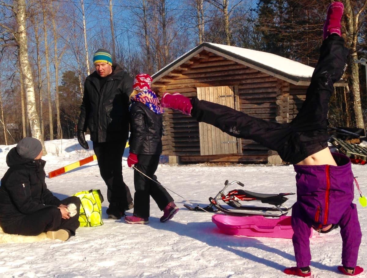Lapsiperhe ulkona aurinkoisessa talvisäässä.  Toinen lapsi vetää pulkkaa, toinen seisoo käsillään.