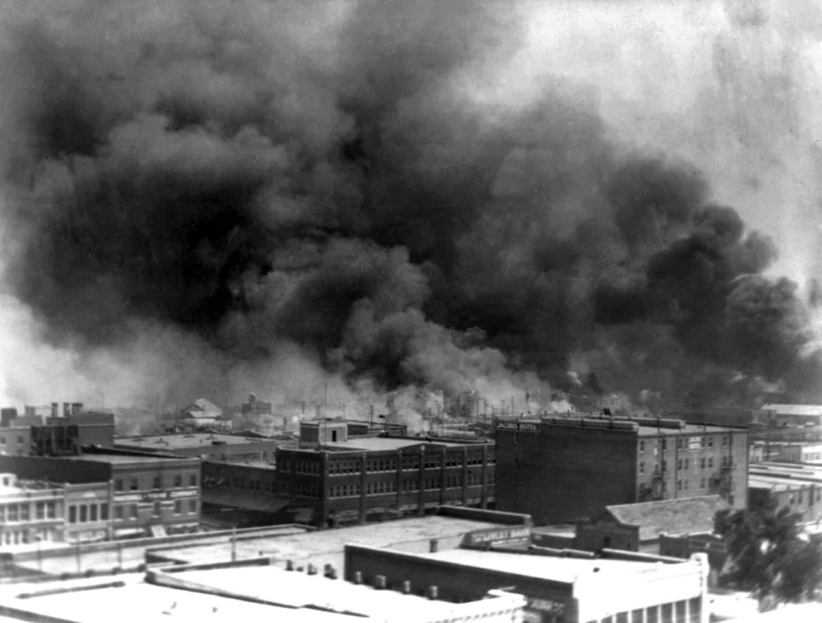 Paksu savu nousee palavista rakennuksista kaupungin ylle.