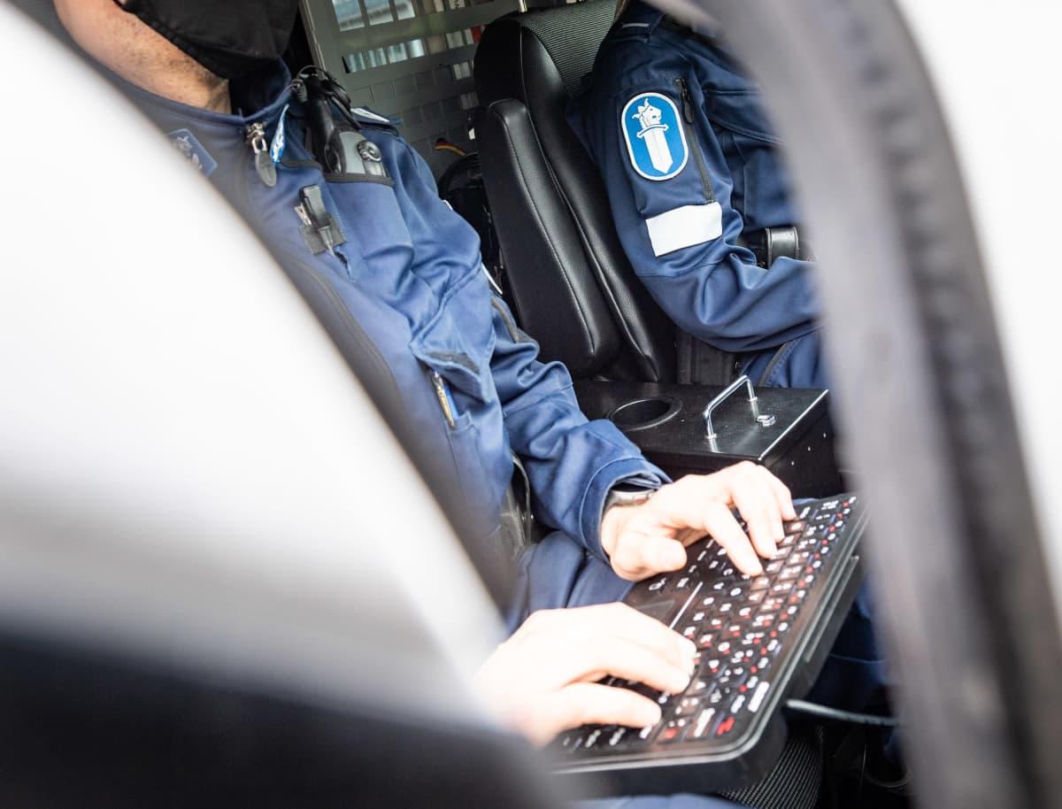 Kaksi poliisia poliisiauton ohjaamossa.