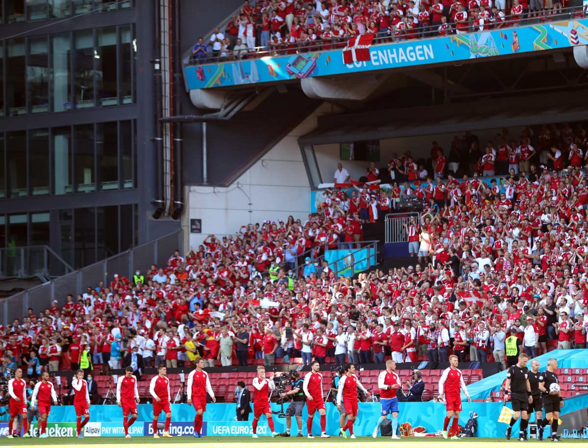 Tanskan joukkueen pelaajat kävelevät stadionilla. Katsomo on täynnä väkeä.