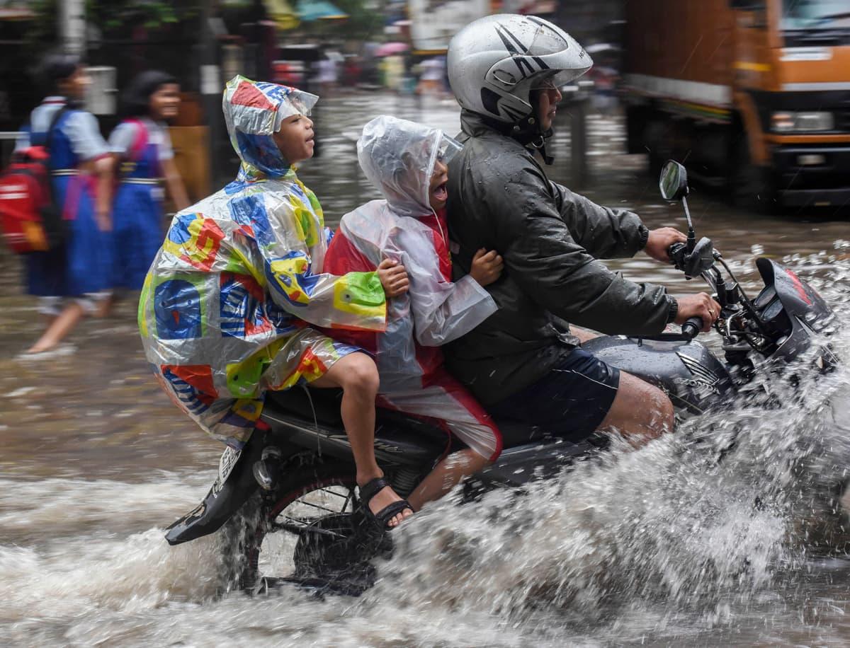 Perhe moottoripyörän selässä tulvivan Mumbain kaduilla.