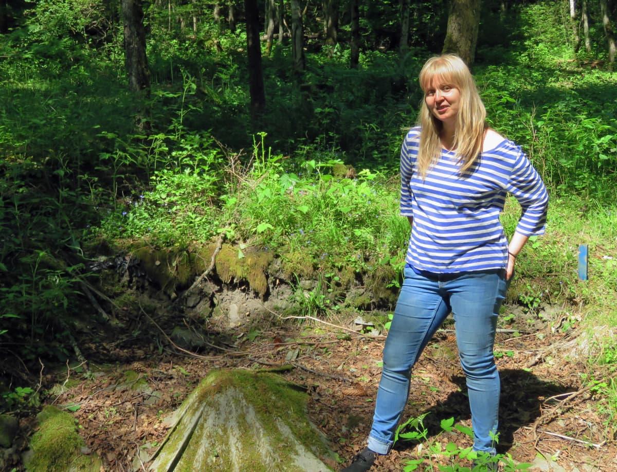 Tuuli Heinonen seisoo arkeologisista kaivauksista jääneessä matalassa kuopassa keskellä vihreää metsää.
