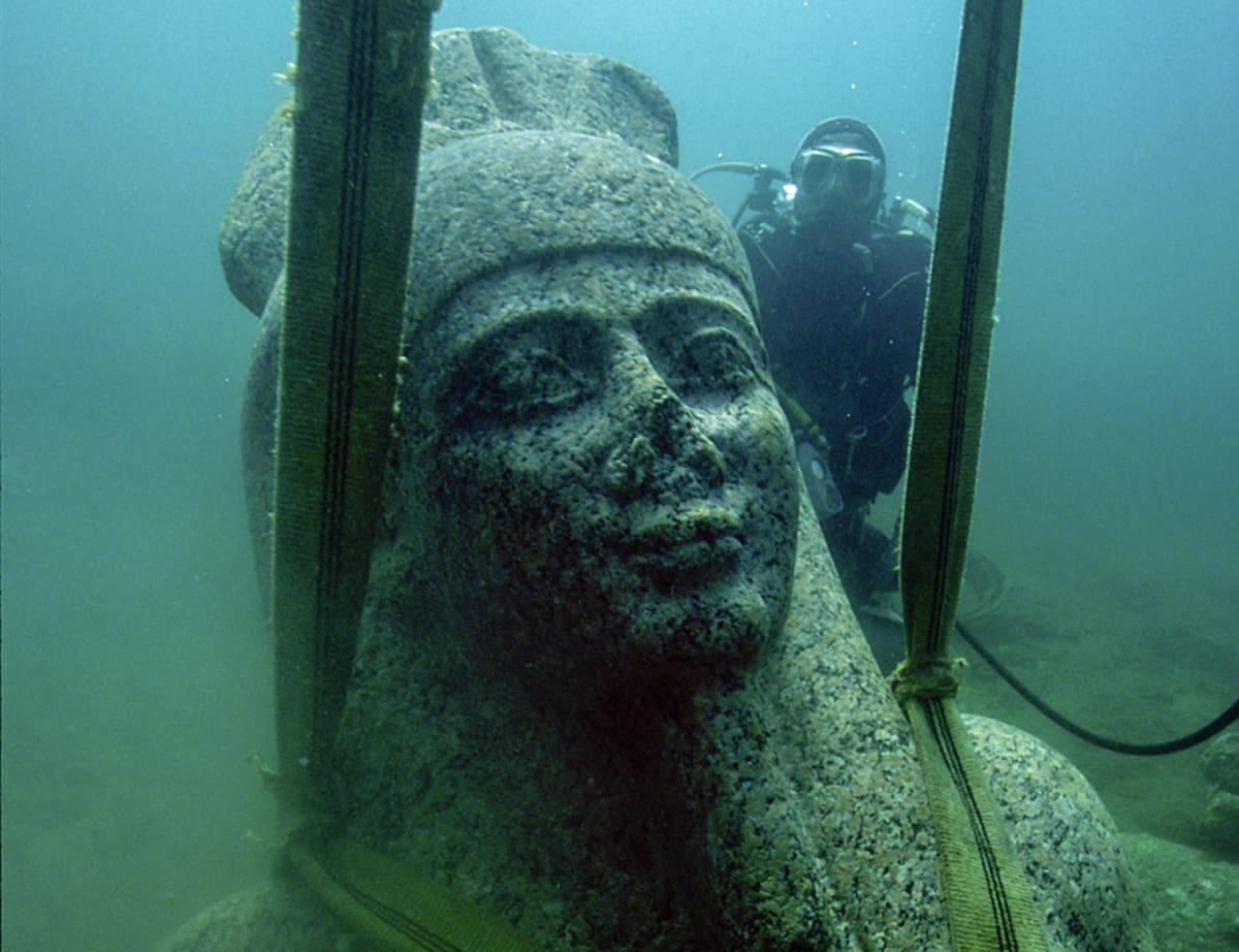 Valtaisiin kiinnitetyn patsaan vieressä uiva sukeltaja on patsaan kasvojen pituinen.