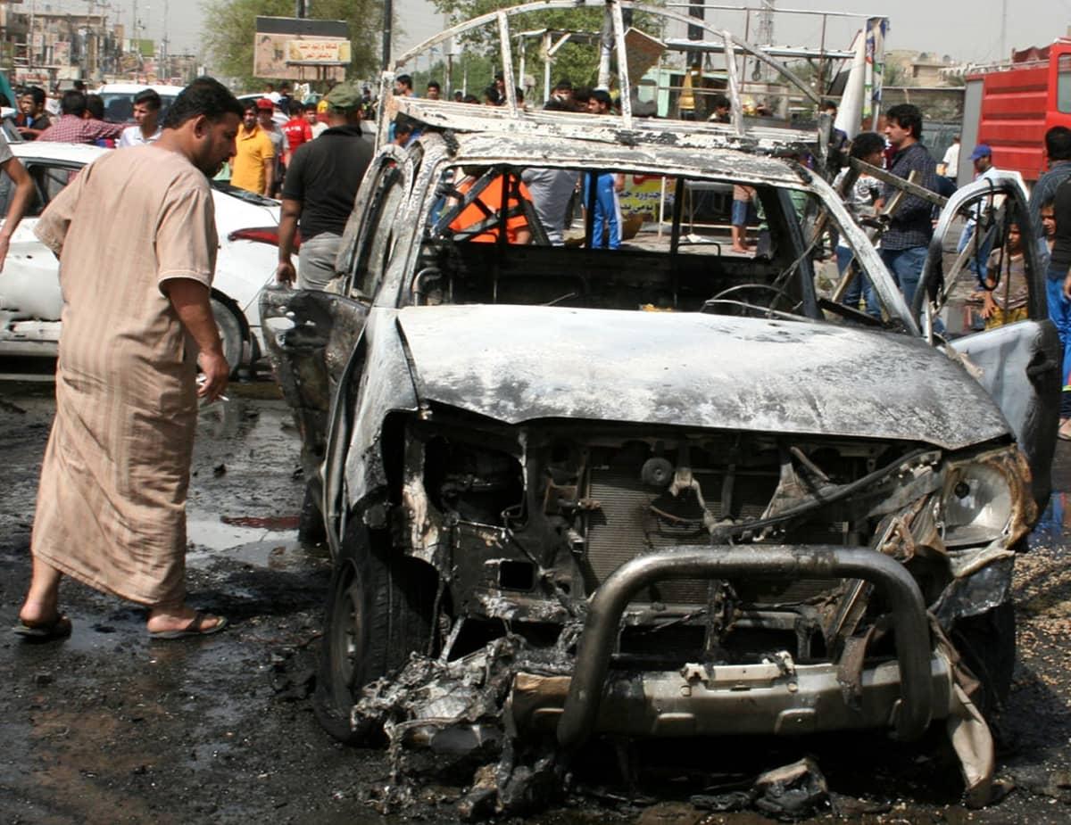 Mies katsoo pommin räjäyttämää autoa Bagdadissa 17. huhtikuuta 2016.