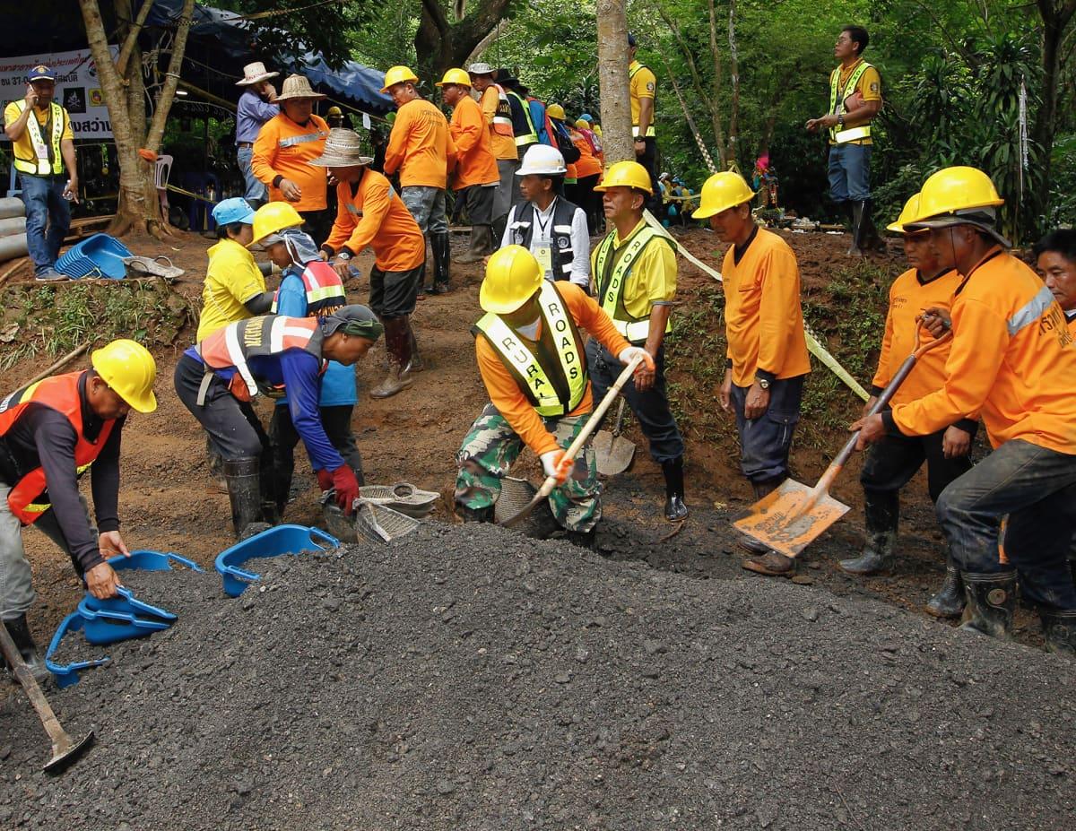 Thaimaalaiset pelastustyöntekijät lapioivat hiekkaa Tham Luang  luolan lähellä.