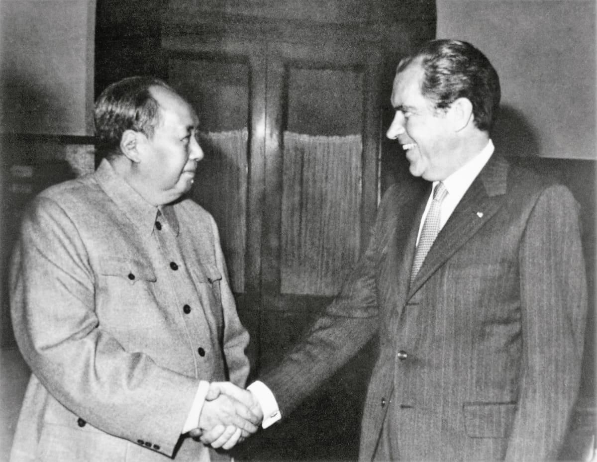 Mao Zeodong ja Richard Nixon kättelevät hymyillen. Maolla on univormunkaltainen yksinkertainen takki, Nixonilla puku, jossa on liituraitoja ja kravatti.Kuva on mustavalkoinen.