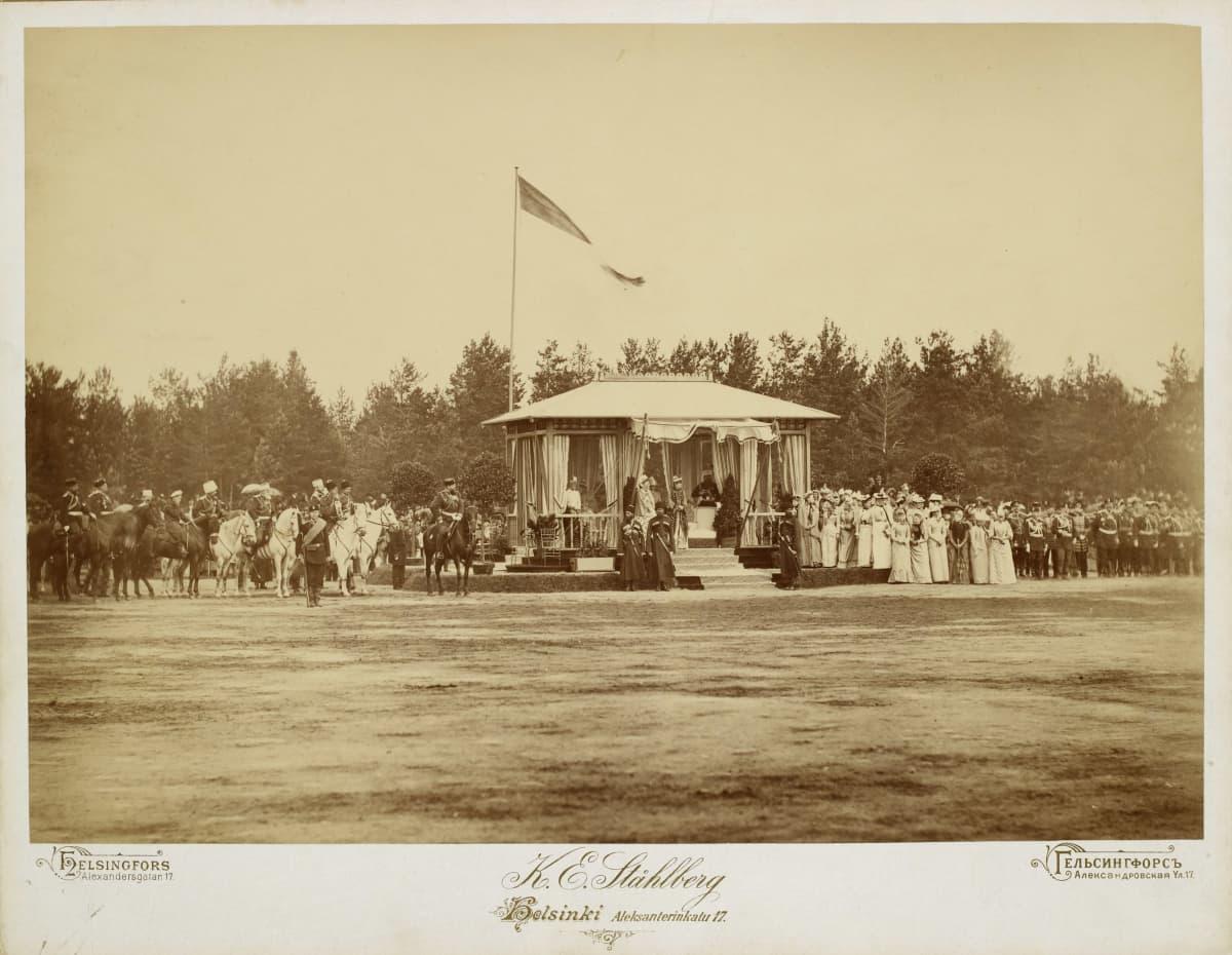keisari Aleksanteri III ratsun selässä korokkeen vieressä mustassa päähineessään. Keisarinna Maria Feodorovna korokkeella keskimmäisenä.