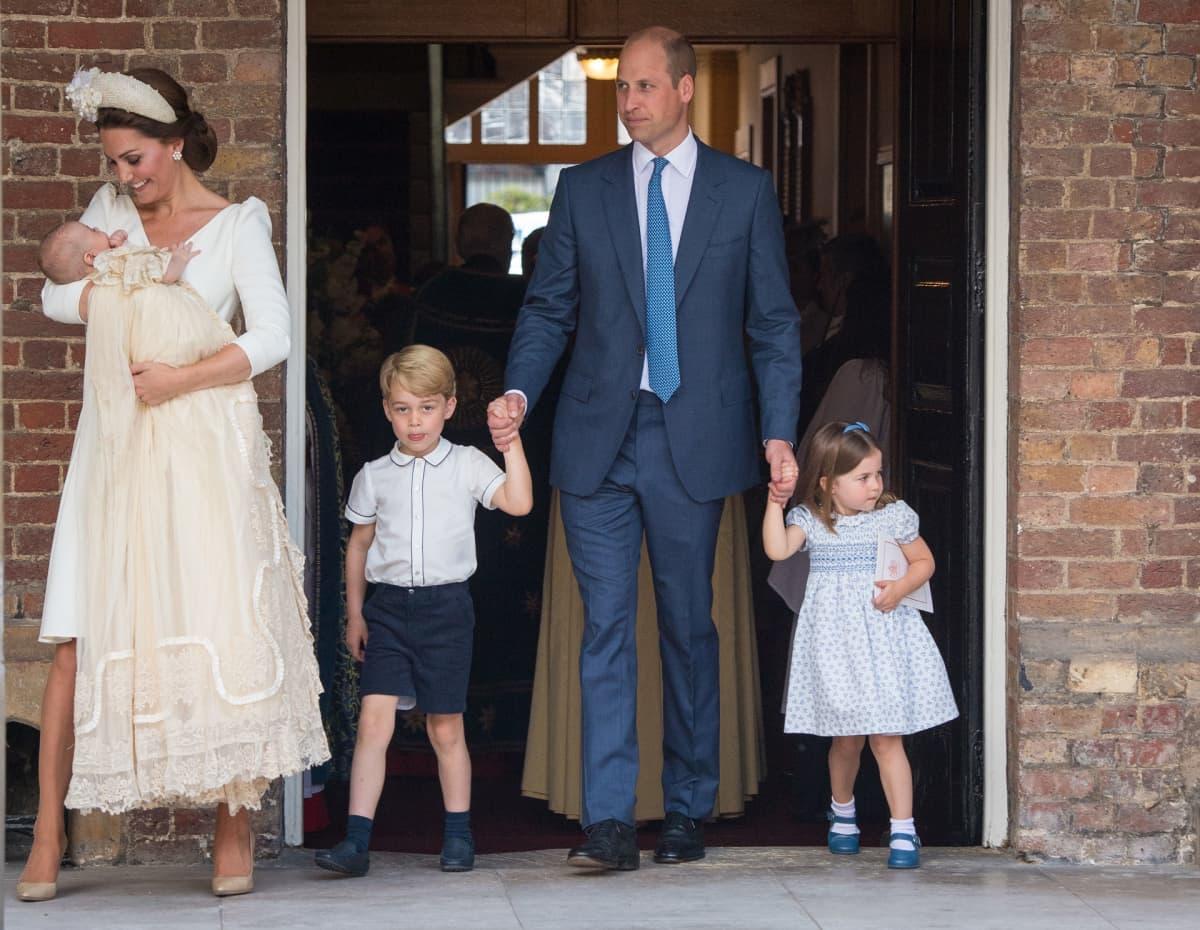 Cambridgen herttuatar Catherine sylissään prinssi Louis, Cambridgen herttua, prinssi William sekä heidän aiemmat lapset prinssi George ja prinsessa Charlotte prinssi Louisin ristiäisissä.