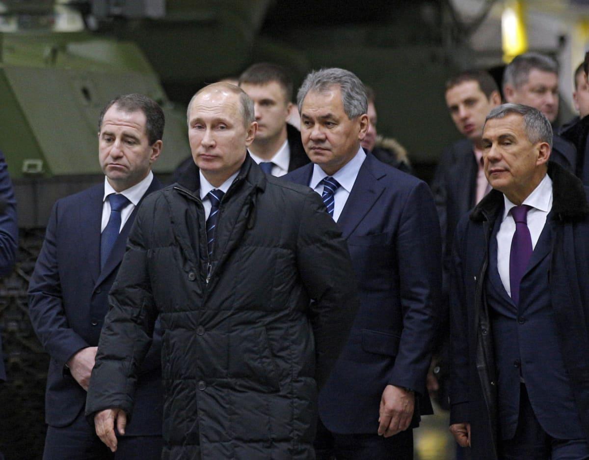 Ryhmä tummiin puettuja miehiä kävelee, taustalla ajoneuvoja.