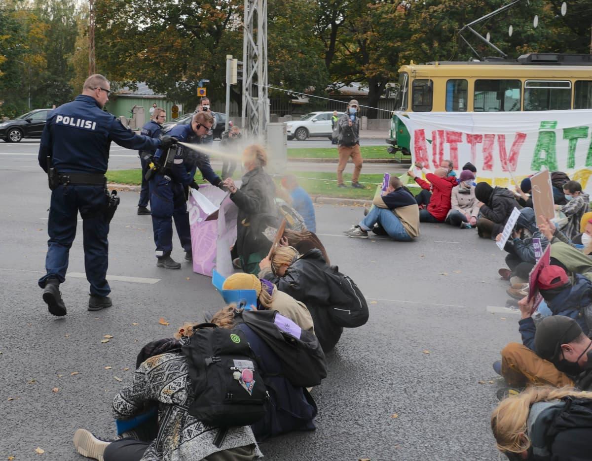 Poliisi sumuttaa mielenosoittajaa.