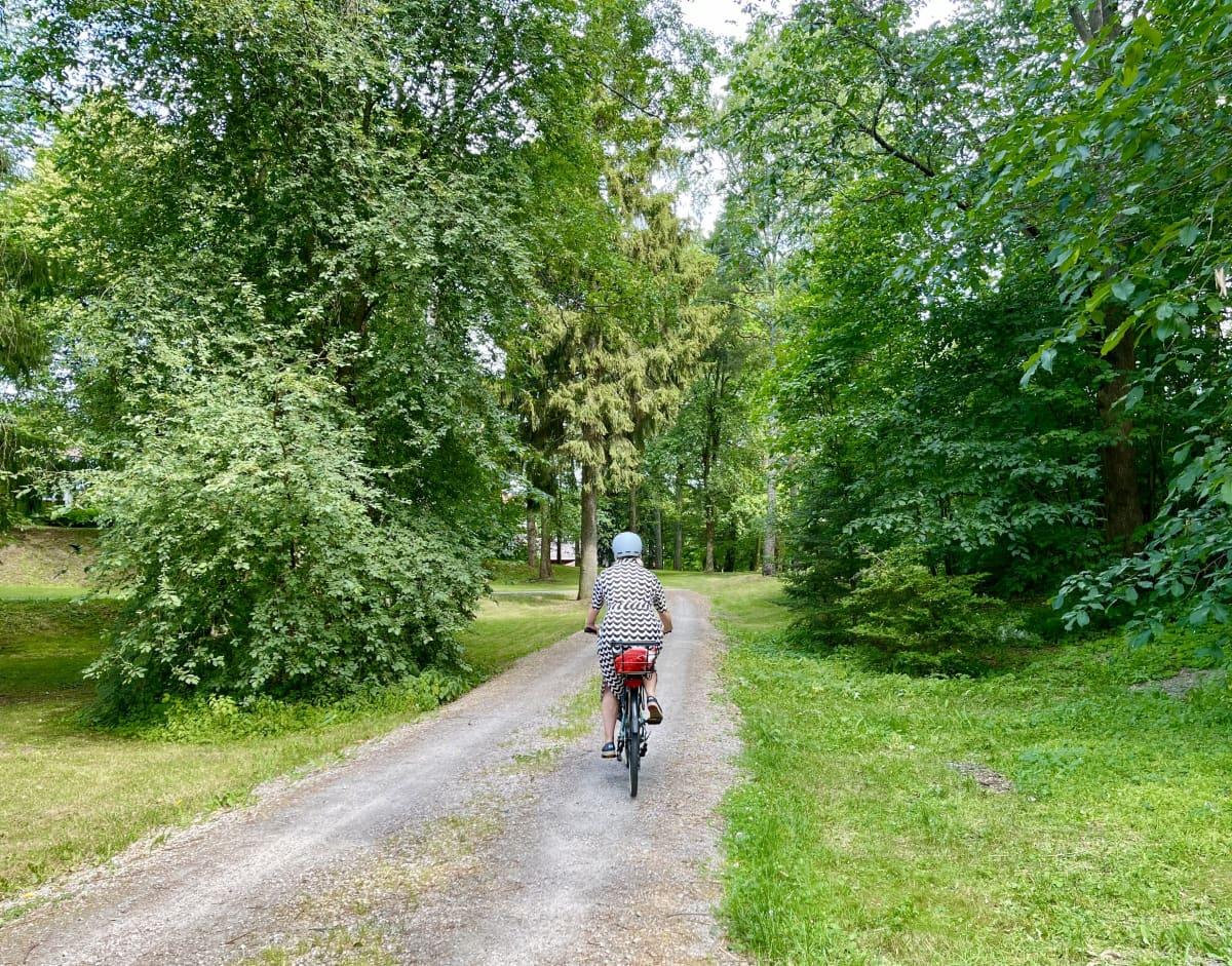Mustavalkoiseen kesämekkoon pukeutunut nainen ajaa polkupyörällä poispäin vihreällä puistotiellä