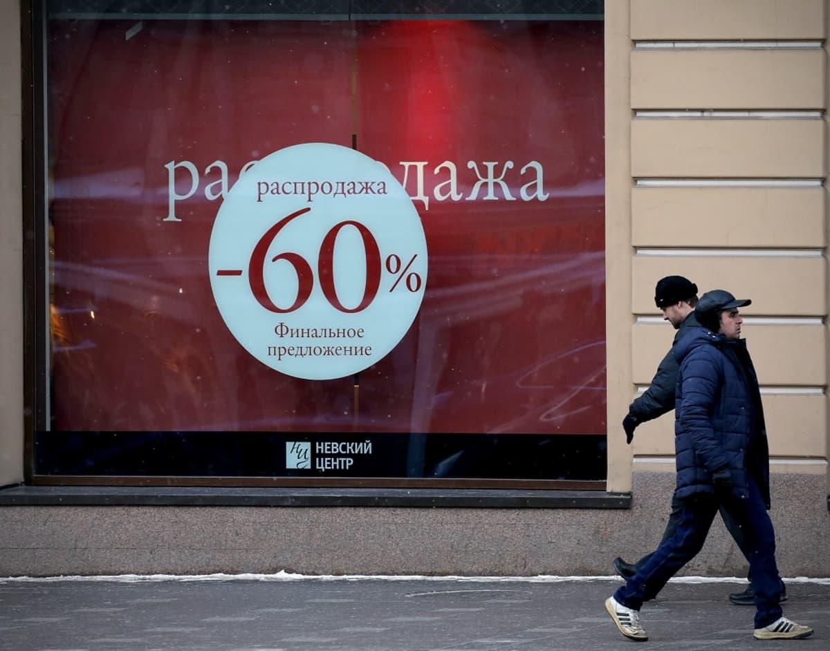 Toppavaatteisiin pukeutuneet miehet kävelivät 60 prosentin alennusmyyntiä mainostavan näyteikkunan ohi Pietarissa sunnuntaina, 24. tammikuuta.