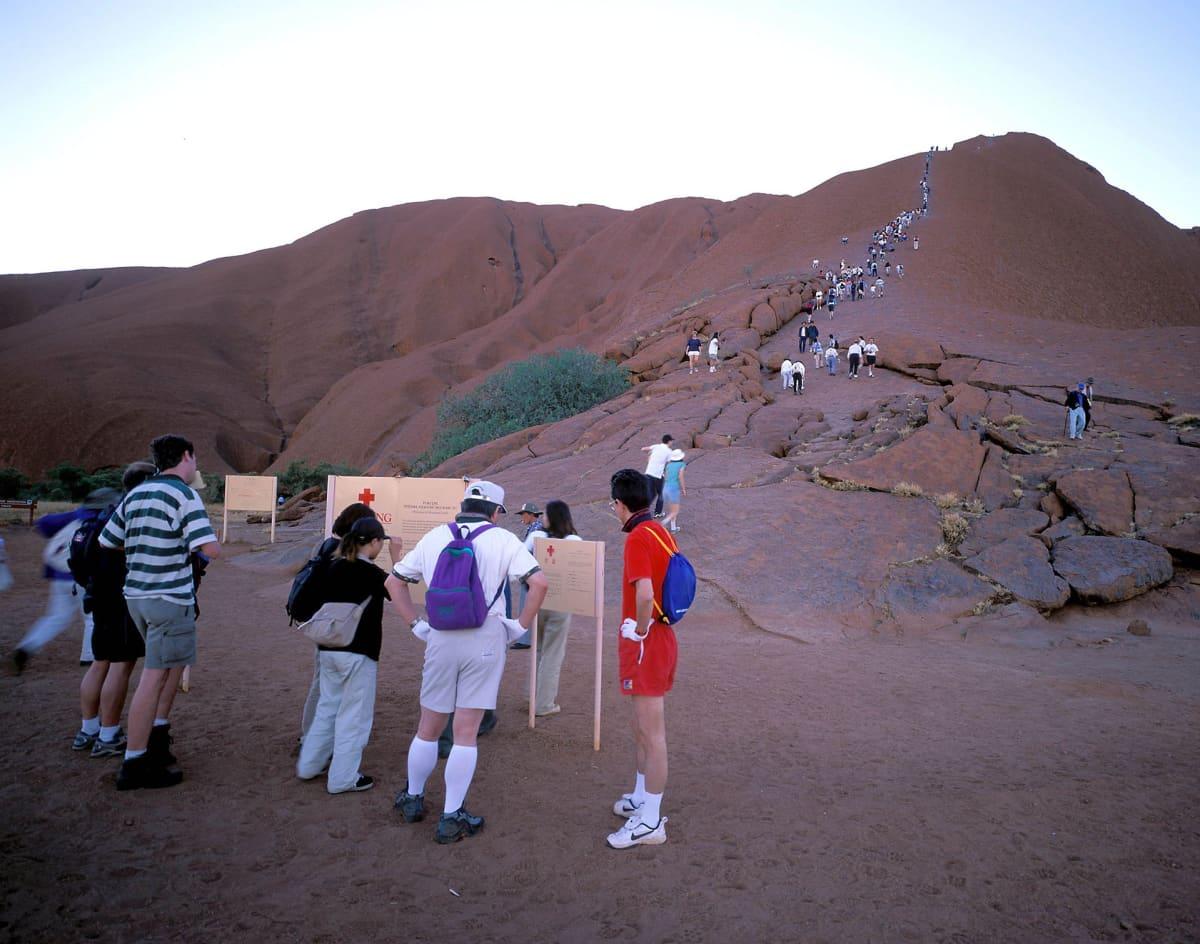 Jono ihmisiä kiipeämässä kalliolle.