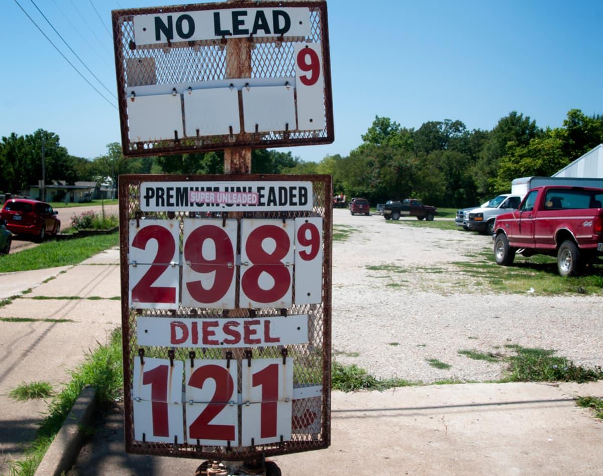 Pysäköityjen autojen edessä on pylväs, jonka taulussa mainostetaan premiumlaatuista lyijytöntä bensiiniä ja dieseliä.