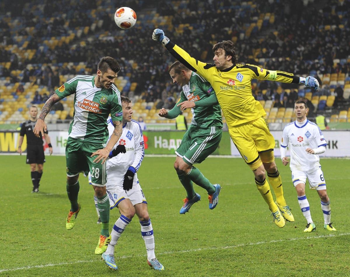 Dynamo Kiovan maalivahti Oleksandr Shokovskiy nyrkkeilee palloon Rapid Wienin pelaajien edestä.