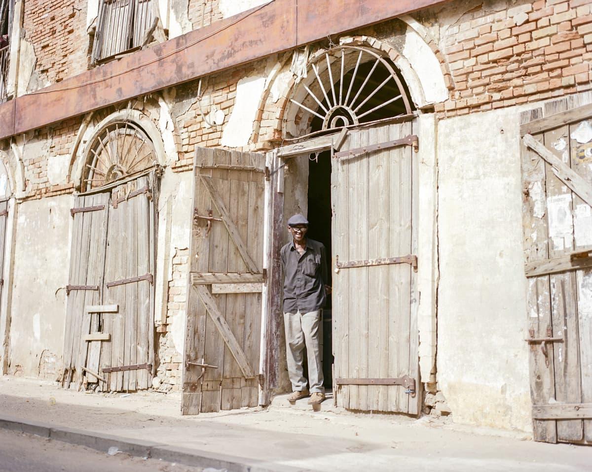 Souleymane Seye seisoo kaksikerroksisen talon edustalla.