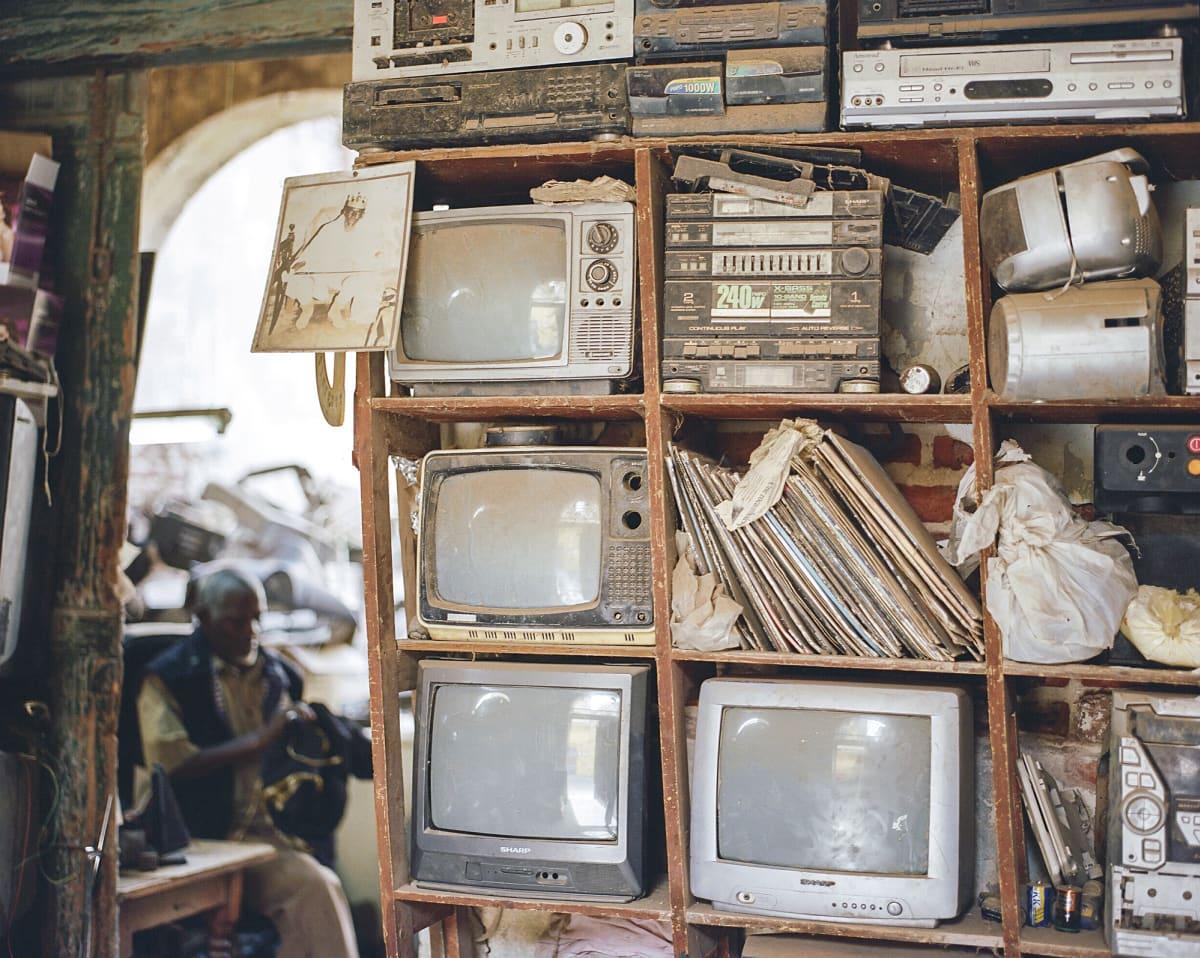 Kuvassa on vanhoja televisioita hyllyssä.