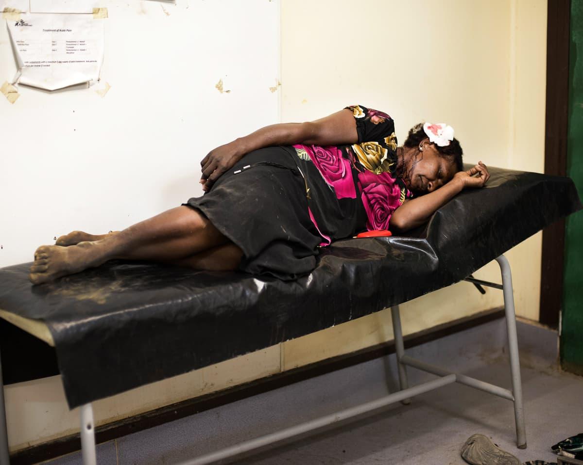 Nainen makaa sairaalasängyllä