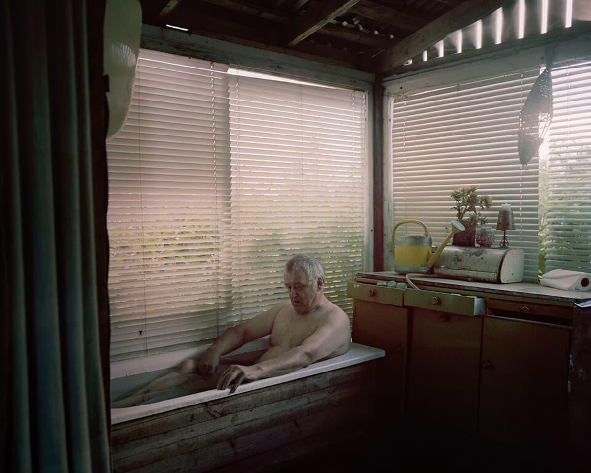 Kainuulaismies istuu ammeessa jonkinlaisessa kesähuoneessa.