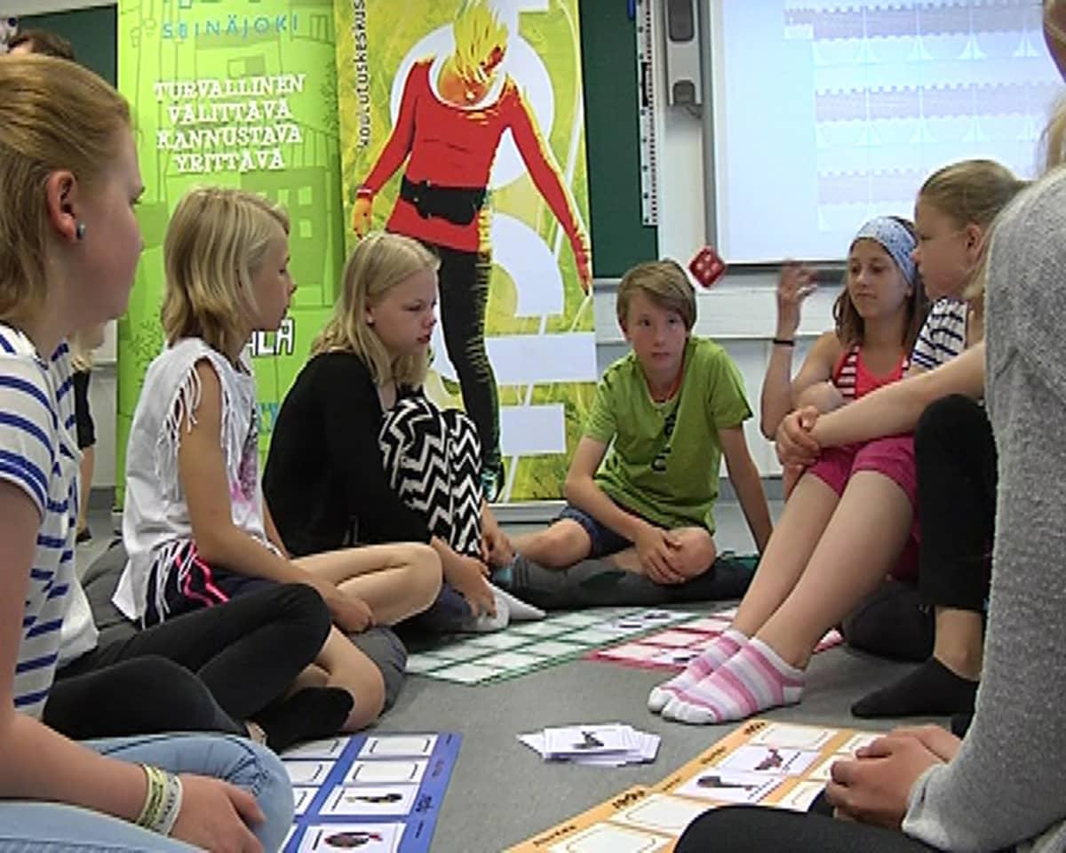 Alakylän koululaiset pelaavat liikunnalllista lautapeliä.
