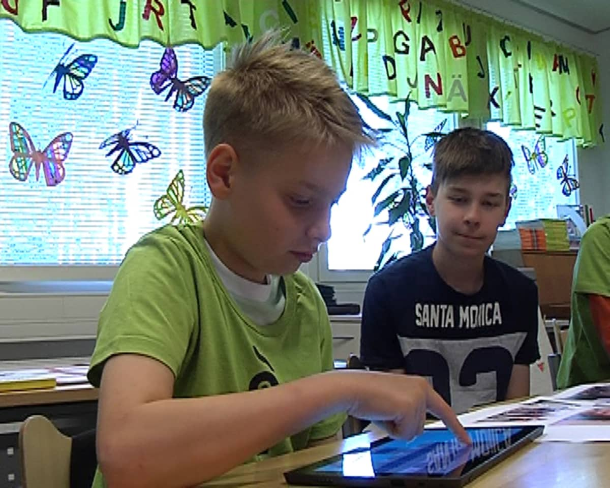 Pojat pelaavat kehittämäänsä muistipeliä tabletilla.