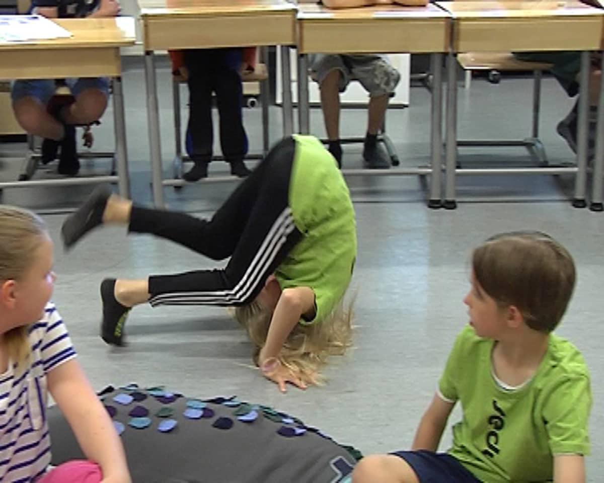 Tyttö tekee kuperkeikan luokkahuoneessa.