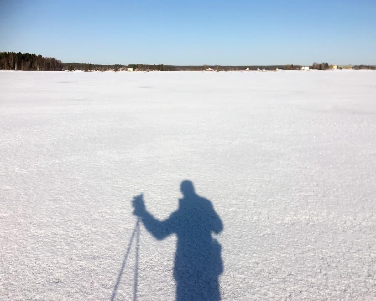 Valokuvaaja Jaakko Heikkilän varjokuva Tornionjoen jäällä maaliskuussa 2020.