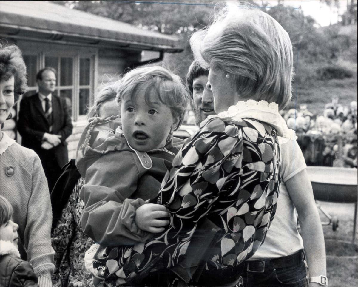 Diana kantaa sylissään kehitysvammaista pientä poikaa.