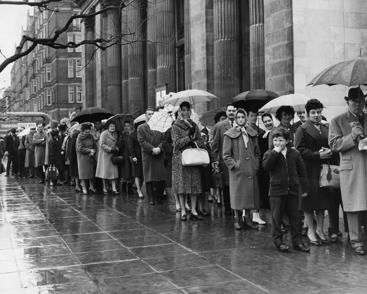 Mustavalkoinen kuva ihmisistä jonottamassa sateisella kadulla.