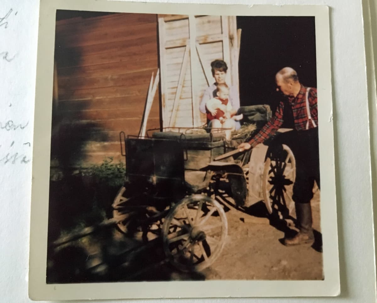 Nainen ja lapsi istuvat vanhoissa hevoskärryissä