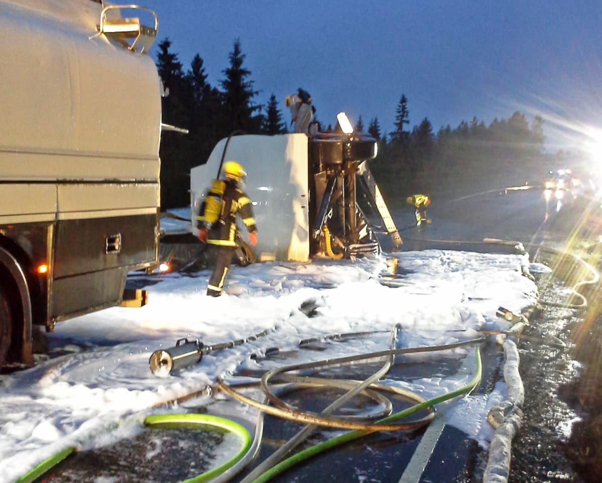 Pelastuslaitoksen työntekijöitä, kaatunut rekan säiliöperävaunu ja letkuja tiellä.