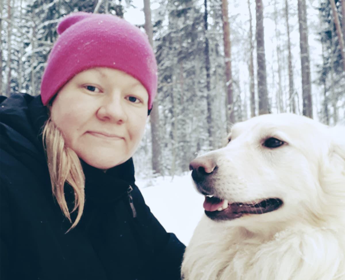 Satu Peltomaa lumisessa metsässä koiran kanssa.