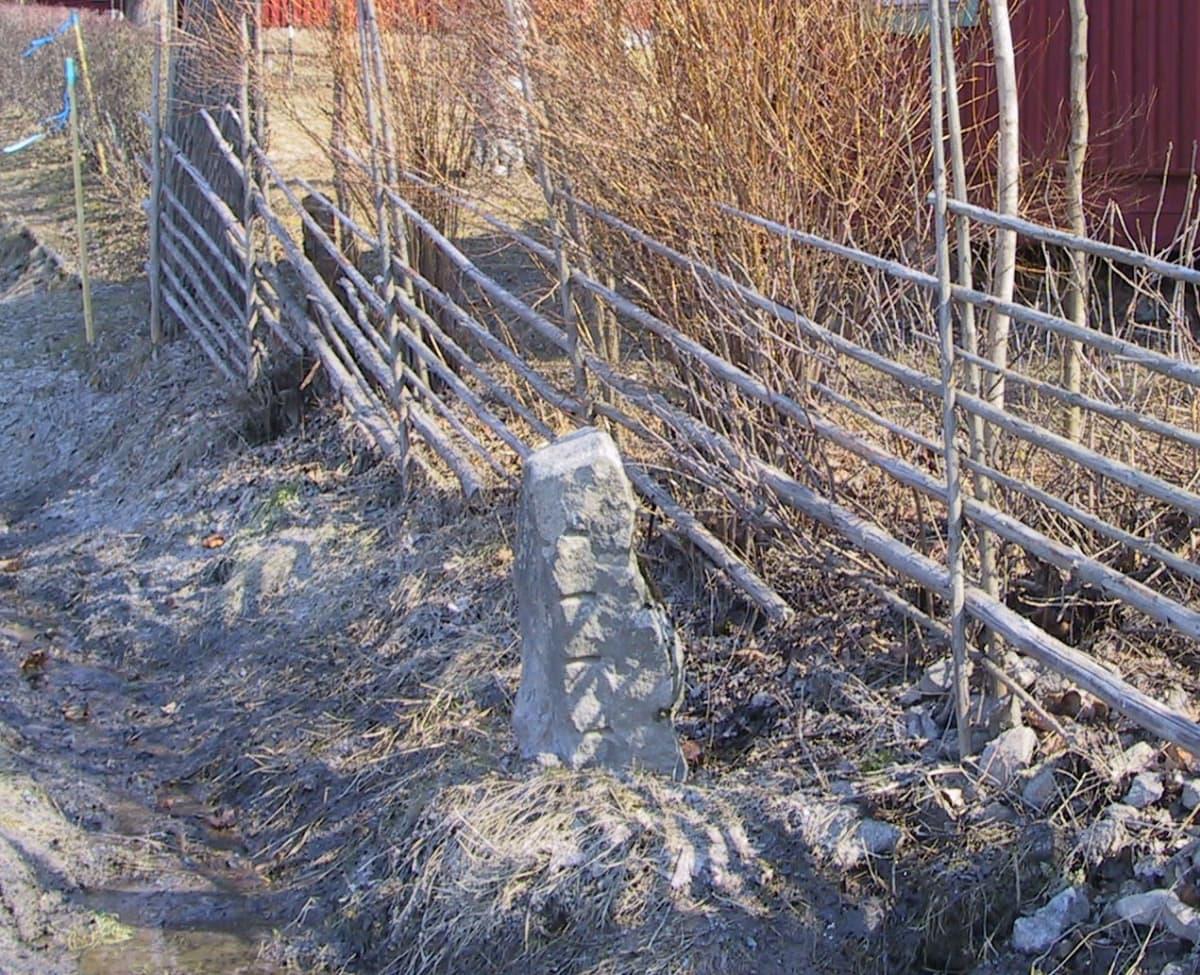 Korkea kivilohkare seiväsaidan vieressä.Lohkareessa näkyy samansuuntaisia pitkiä uurteita yhdessä nurkassa.